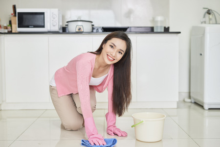 Young happy woman is cleaning the house.