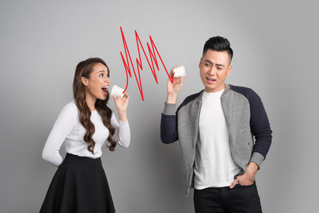 Young asian couple with can phone isolated on gray background Stockfoto