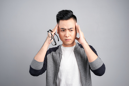 A young man holding his head with fingers in both hands looking down looks tired with a headache, isolated on a gray background.
