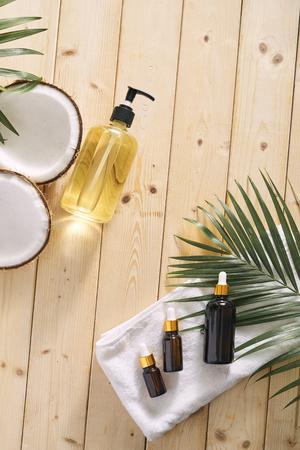 Coco agrietado y una botella de aceite en la mesa - concepto de spa, cuidado de la piel, cuidado del cabello y relajación