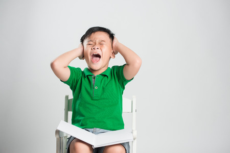 Young boy and closed eyes covering ears with hands Stock Photo