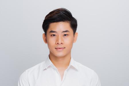 Hombre guapo asiático, sonriendo y riendo aislado sobre fondo blanco, enfoque suave Foto de archivo
