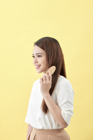Portrait of cute young woman on yellow background combing hair.