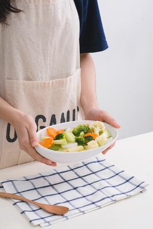 Fresh vetgetables,carrots,long beans, boiled corn in hand on white table