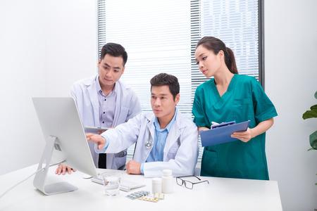 Drie artsen bespreken patiëntendossiers op kantoor. Stockfoto