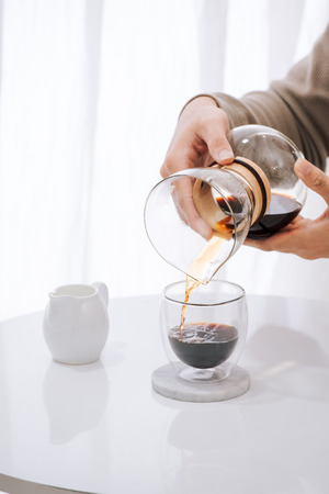 Brewing nel drip coffee. Step by step cooking instructions. Coffee is ready. Barista pouring brewed coffee in the cup Foto de archivo - 118430647