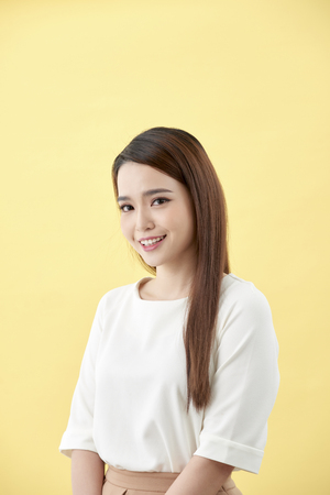 Asian woman smiling with dimple long hair black eyes on yellow background