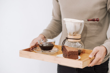 Drip coffee on wooden tray with chocolate cake. Coffee time on the cafe with natural light