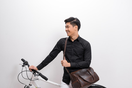 handsome young man with shoulder bag and bicycle standing isolated on white background 版權商用圖片