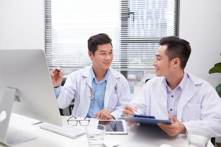 Hardworking doctors reviewing patient's file Imagens