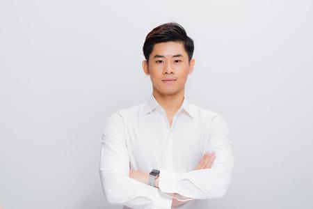 Hombre asiático en camisa, mirando a cámara, con las manos juntas Foto de archivo