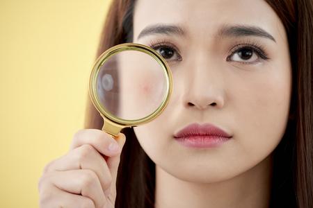 Frau mit Lupe auf gelbem Hintergrund isoliert Standard-Bild