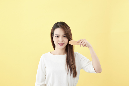 Portrait of attractive smiling woman brushing her hair isolated on yellow studio shot Foto de archivo - 122835449