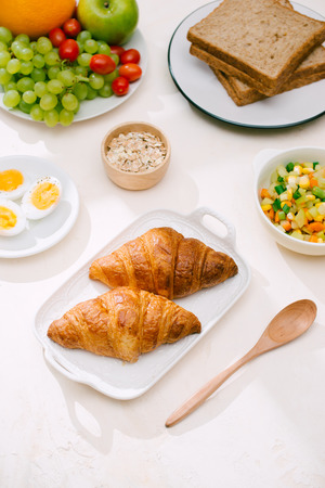 Healthy Breakfast served with milk, croissants, egg, cereals, oatmeal and fruits. Stock Photo