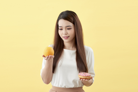 Portrait of a smiling young asian woman choosing between donut and orange isolated over yellow background