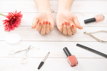 Female hands with red manicure and an open bottle of varnish on the table 스톡 콘텐츠 - 118824256