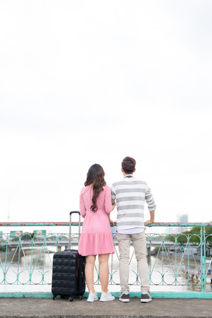 Couple with suitcase standing in the city and looking around