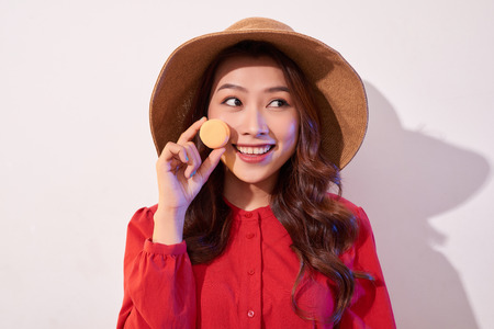 Young woman standing with french sweet cookie macaron over white background 写真素材