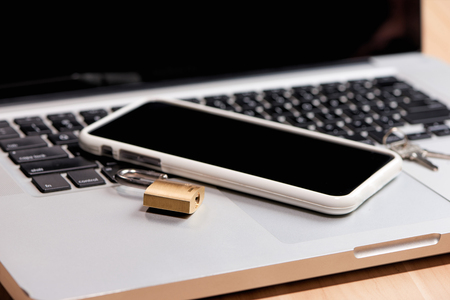 Smartphone and padlock is lying on a laptop keyboard 版權商用圖片