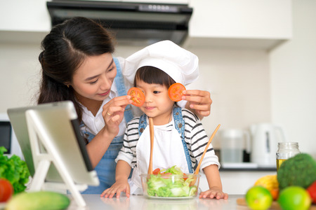 Happy family in the kitchen. Mother and child daughter are preparing the vegetables and fruit. Stockfoto