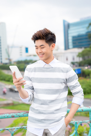 Young asian handsome businessman smiling while reading his smartphone. Portrait of asian business man reading message with smart phone in outdoor. Imagens