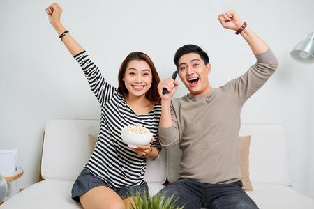 Jeune beau couple bénéficiant de temps libre à regarder la télévision avec du pop-corn Banque d'images