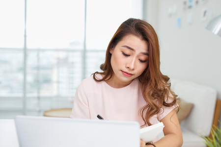 Puzzled confused asian woman thinking hard concerned about online problem solution looking at laptop screen, worried serious asian businesswoman focused on solving difficult work computer task