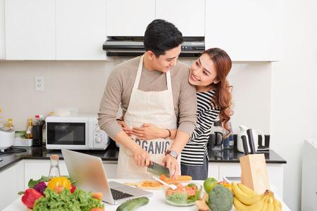 Couple d'amoureux cuisinant ensemble dans la cuisine à la maison