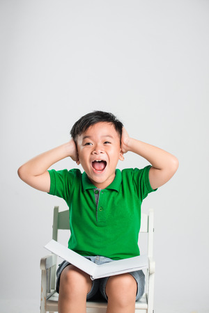 Young boy with closed eyes covering ears with hands Stock Photo