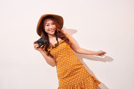 Image of young photographer woman isolated over beige background wall holding camera.