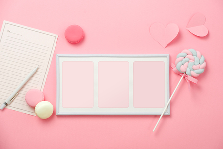 A white sheet of paper for message to loved one, candy with picture frame on pink background. Happy woman's day concept. Mock up