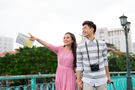 Young happy Asian couple tourist enjoy on summer holiday traveling in Saigon, Vietnam