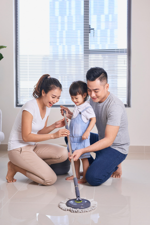 Ordinary family of three doing house cleaning with cleaning equipment Stock Photo