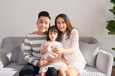 happy parents with cute little daughter sitting on couch and smiling at camera Stockfoto