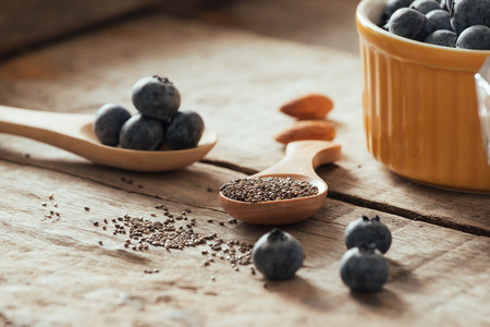 Fresh blueberries and chia seeds on a old wooden table