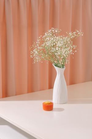 Gypsophila (Babys breath flowers), in bottle on textured background. Beautiful light, airy masses of small white flowers. floral still life as Interior decoration concept.