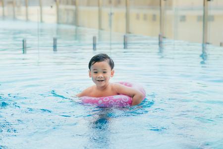 Sweet little boy, swimming in big swimming pool, summertime