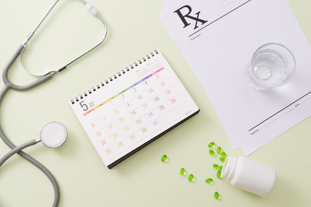Stethoscope with drugs and pills on calendar page