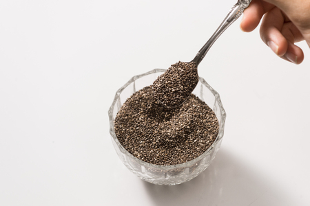Man Pouring a Spoonful of Chia Seed into a Glass Container