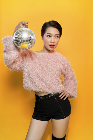 Portrait of charming young female showing tongue and fooling around holding mirror ball on head posing on yellow background. Party and glitter fashion concept Stock Photo