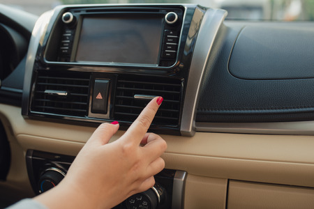 Woman turns on air conditioning in the car. Modern car interior Stock Photo