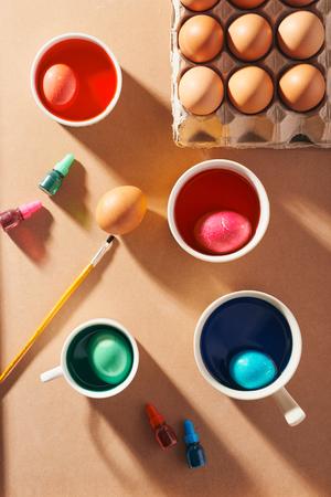 A dozen eggs in a carton, used watercolor paints. Stockfoto