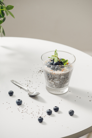 Healthy breakfast or morning snack with chia seeds vanilla pudding and berries on wooden background, vegetarian food, diet and health concept