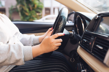 Asian female hands on the steering wheel of a car while driving with windshield and road. Black woman hands holding a steering wheel confidently. Hands on wheel - Woman driving car - Asia Stockfoto - 118849498