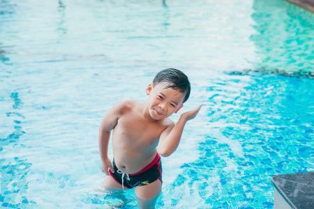 Enfant asiatique mignon nettoyant les oreilles après avoir nagé dans une piscine