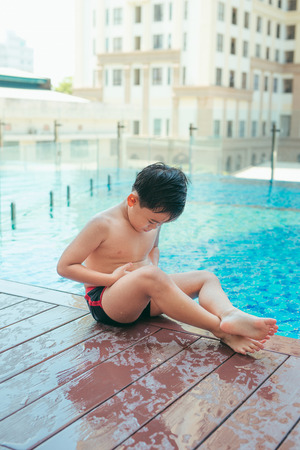 Asian cute child swimming in swimming pool. He playing is funny on summer holiday on blurred background. Cute boy smile and swim on daytime and light of sun. It joyful vacation for him.