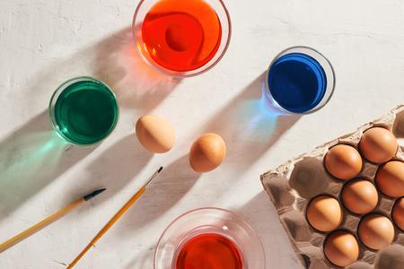 A dozen eggs in a carton, used watercolor paints. Фото со стока