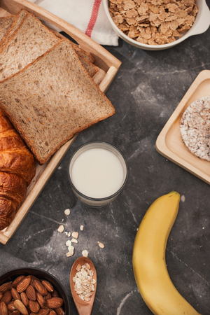 Photo of bread, bun, milk, almonds and fresh milk on table with skin color background. Breakfast preparation, daily product. Фото со стока