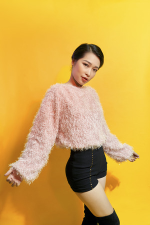 Short-haired girl in fashionable dancing. Young playful female model in stylish fur outfit. Beautiful happy woman having fun dance in studio on yellow Stock Photo