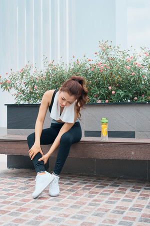 young beautiful and fit sport woman after running workout sitting on park bench happy and relaxed in healthy lifestyle concept